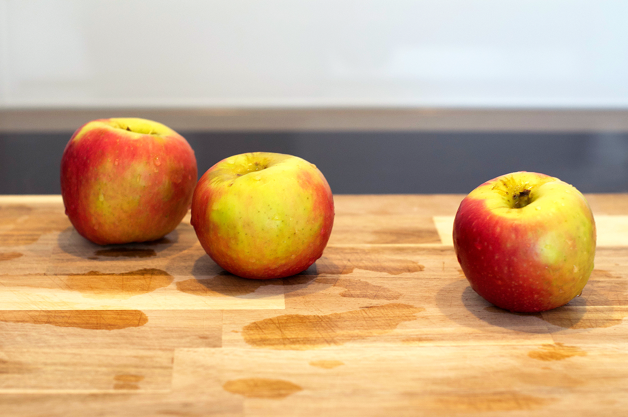 Three pink lady apples on wooden chopping board