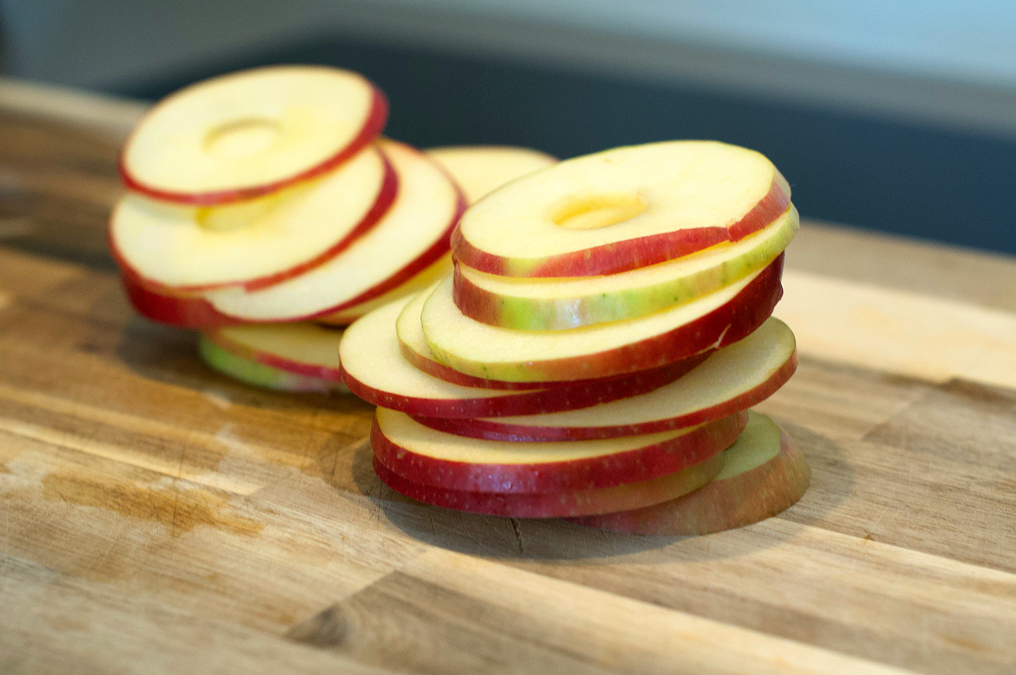 Cored and sliced pink lady apples on wooden chopping board